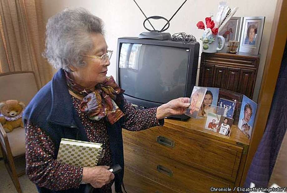 WBHOME11b-C-04APR03-SF-LM  Sydney Nakamura, a resident of Kimochi Home, which is celebrating its 20th anniversary of providing residential and respite care for the Japanese American community. Her she looks over pictures of her kids and grandkids in her room. Photo by Liz Mangelsdorf/sf chronicle Photo: Liz Mangelsdorf