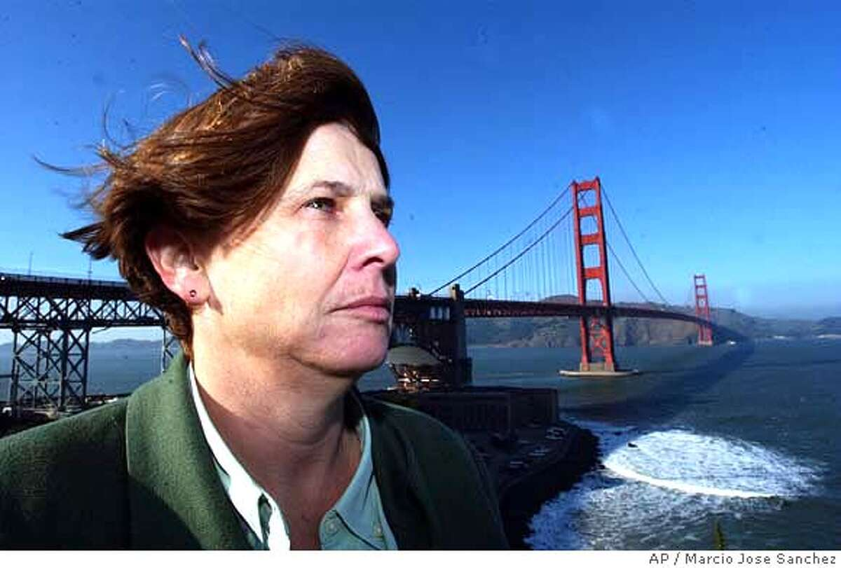 Mary Currie, spokeswoman for the agency that administers and maintains the Golden Gate Bridge, poses near the landmark in San Francisco, Wednesday, Jan. 19, 2005. A film project was proposed as a documentary intended to