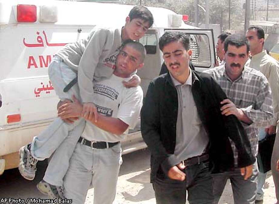 A wounded boy is carried into the hospital in the West Bank town of Jenin after an explosion in a high school in the nearby village of Jaba which injured at least 29 students Wednesday April 9, 2003. One of the students at the school was playing with the explosive device before it exploded, police said. (AP Photo / Mohamad Balas) Photo: MOHAMAD BALAS
