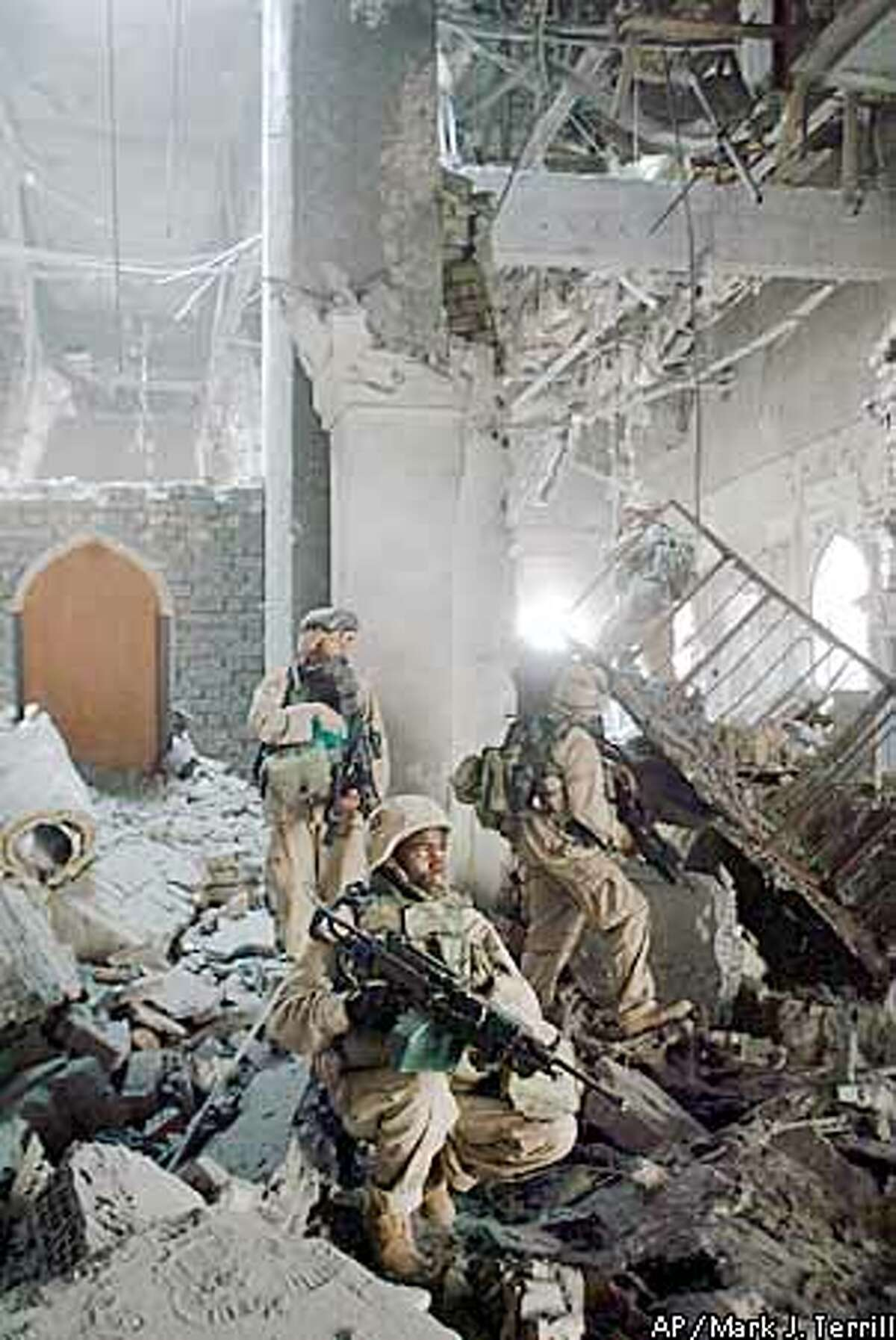 U.S. Army soldiers from A Company, 3rd Battalion, 7th Infantry Regiment, search one of Saddam Hussein's palaces damaged after a bombing, in Baghdad Monday, April 7, 2003. Coalition soldiers took over key buildings Monday, as gunfire and explosions thundered in many parts of the battered Iraqi capital. (AP Photo/John Moore)