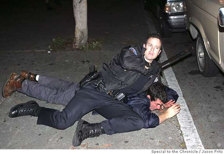 SFPD officer tackles a protester on 23rd street near Mission late Friday evening.  Special to the Chronicle/ Photo by Jason Fritz (one-time use, phone 415-370-1660)