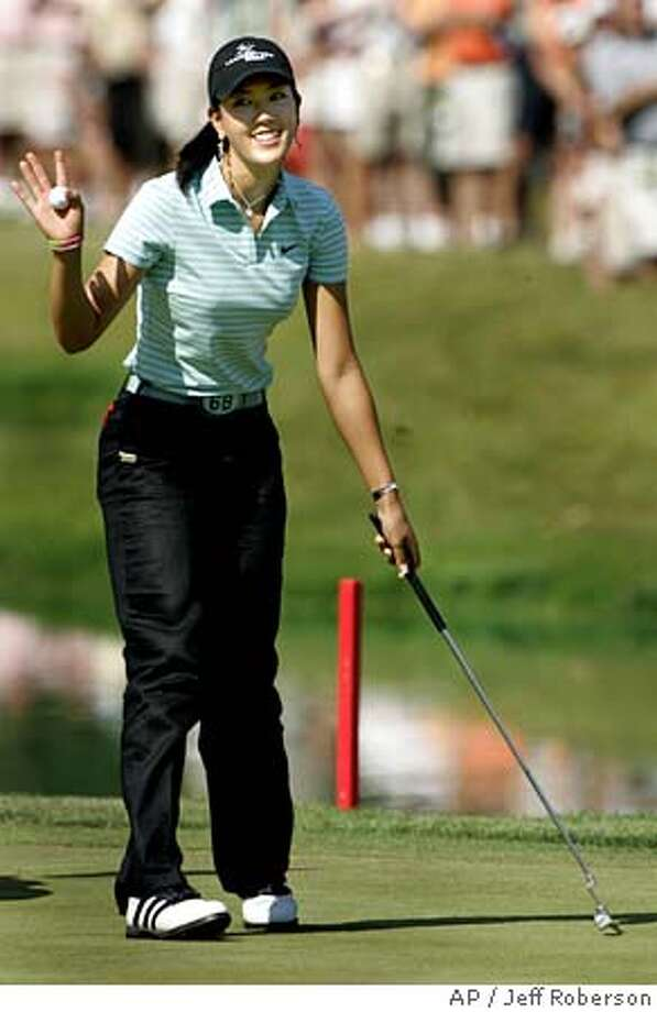 Amateur golfer Michelle Wie smiles to a cheering crowd after sinking a very short putt for birdie on the 18th green during the second round of the PGA John Deere Classic Friday, July 8, 2005 in Silvis, Ill. (AP Photo/Jeff Roberson) Photo: JEFF ROBERSON