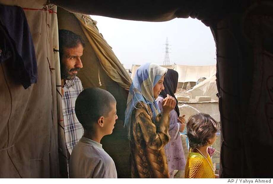 �** ADVANCE FOR SUNDAY APRIL 30 ** A Kurdish Shiite family looks out of their tent in northwestern Iraq refugee camp after having fled threats and sectarian violence in Baghdad, Tuesday April 25, 2006 in Khanaqin 140 km (87 miles) northeast of Baghdad, Iraq. Three Years ago Monday, President George Bush declared the United States had done what it intended in Iraq - removed a tyrant and freed a people; but despite progress toward democracy, the rebuilding of some parts of the land and the best efforts of its own people and an international coalition - the battle for Iraq's future had only just begun.(AP Photo Yahya Ahmed) HFR 04-30-06. ADVANCE FOR SUNDAY, APRIL 30 Photo: YAHYA AHMED