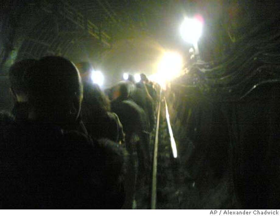 In this image provided by commuter Alexander Chadwick, taken on his mobile phone camera, passengers are evacuated from an underground train in a tunnel near Kings Cross station in London, Thursday, July 7, 2005. At least 33 people were killed Thursday in three explosions in London's subway system, a senior police official said. Deputy Assistant Commissioner Brian Paddick said others died in an explosion on a bus in central London but gave no figures. The second blast, at 8:56 a.m. (0756GMT), in the King's Cross area of north London, killed 21, Paddick said. (AP Photo / Alexander Chadwick) Photo: ALEXANDER CHADWICK