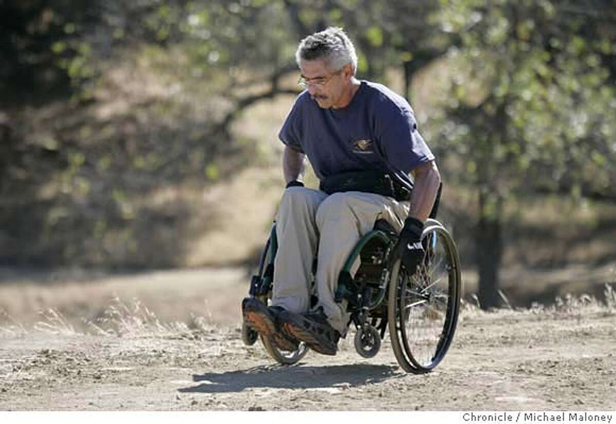 """WHEELCHAIR_35_MJM.jpg Bob Coomber hikes at one of his favorite hikes - the trails of Morgan Territory Park near Livermore. Bob Coomber is wildland enthusiast. He spends most of his free time in the east bay parks or Sierra, exploring the wide open spaces. He is also a paraplegic, and his excursions are all conducted via an all-terrain wheelchair. Coomber is an activist for making more of the wilderness wheelchair accessible, but only, he says, in a """"gentle"""" way. He feels many areas are inappropriate for improved trails, and he wants only minimal grading for those areas where they make sense. Folks in wheelchairs, he feels, have to be up to the challenge, conditioning themselves to handle the wilderness. Photo by Michael Maloney / San Francisco Chronicle Ran on: 10-18-2004 Bob Coomber crests a hill on one of his favorite hikes, a 6-mile loop in the Morgan Territory Regional Preserve east of Mount Diablo. MANDATORY CREDIT FOR PHOTOG AND SF CHRONICLE/ -MAGS OUT"""