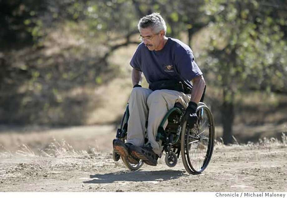 "WHEELCHAIR_35_MJM.jpg  Bob Coomber hikes at one of his favorite hikes - the trails of Morgan Territory Park near Livermore.  Bob Coomber is wildland enthusiast. He spends most of his free time in the east bay parks or Sierra, exploring the wide open spaces. He is also a paraplegic, and his excursions are all conducted via an all-terrain wheelchair. Coomber is an activist for making more of the wilderness wheelchair accessible, but only, he says, in a ""gentle"" way. He feels many areas are inappropriate for improved trails, and he wants only minimal grading for those areas where they make sense. Folks in wheelchairs, he feels, have to be up to the challenge, conditioning themselves to handle the wilderness. Photo by Michael Maloney / San Francisco Chronicle Ran on: 10-18-2004  Bob Coomber crests a hill on one of his favorite hikes, a 6-mile loop in the Morgan Territory Regional Preserve east of Mount Diablo. MANDATORY CREDIT FOR PHOTOG AND SF CHRONICLE/ -MAGS OUT Photo: Michael Maloney"