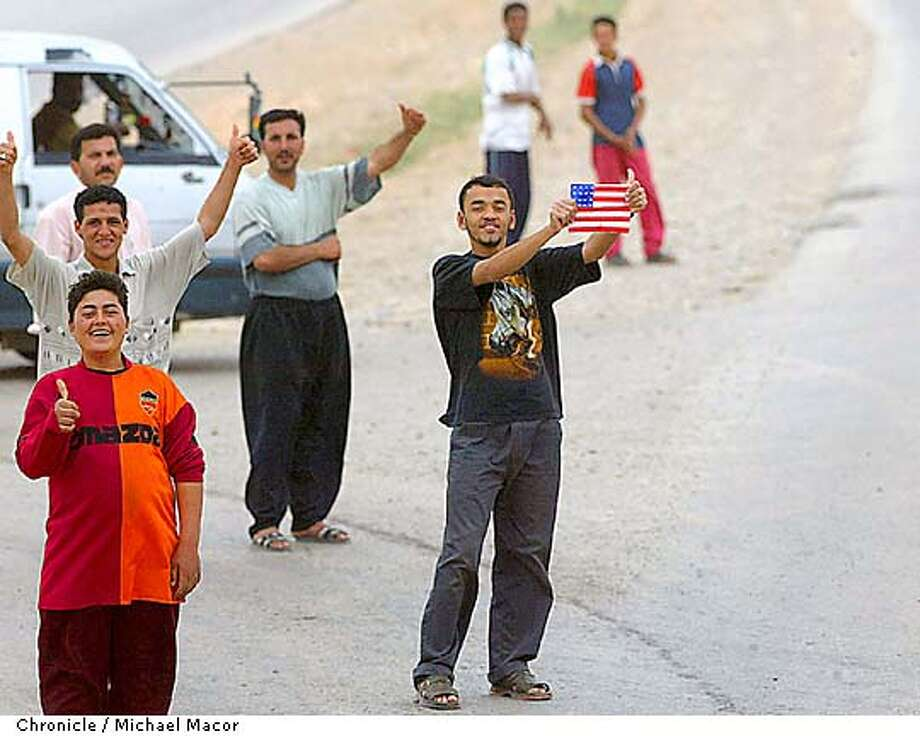 Iraqi's give the thumbs up and American flags to US Military as they pass throough towns south of Baghdad. by Michael Macor/The chronicle Photo: MICHAEL MMACOR