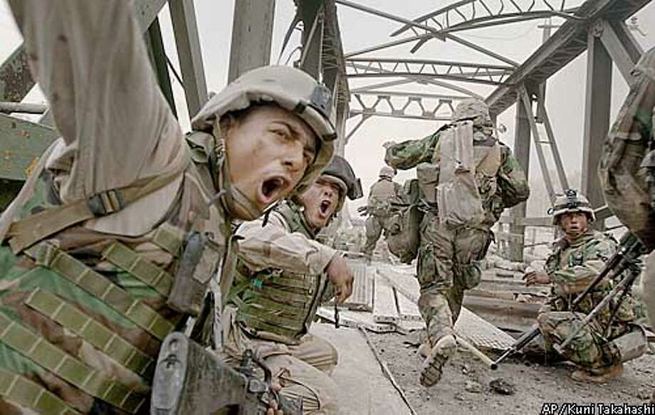 U.S. Marines from the 3rd Batallion yell to urge infantrymen to rush across the damaged Baghdad Highway Bridge, Monday, April 7, 2003, as they move forward into the city while under fire in the southeastern outskirts of Baghdad. (AP Photo/Boston Herald, Kuni Takahashi) ** MANDATORY CREDIT ** Photo: KUNI TAKAHASHI