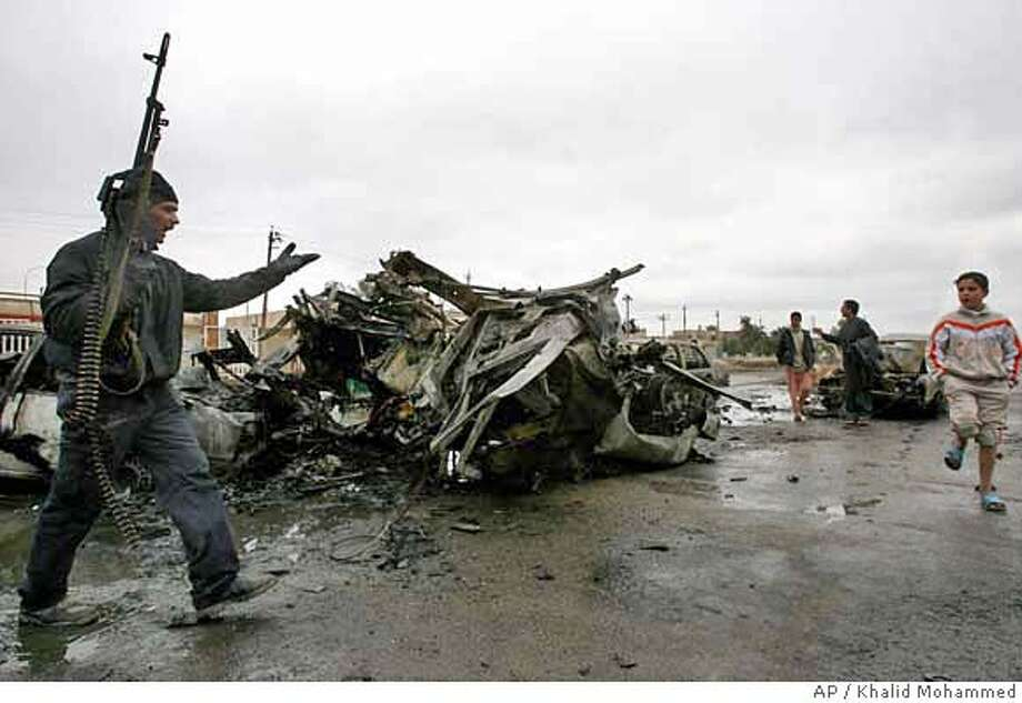 An Iraqi police officer tries to keep bystanders away from the scene of a car bomb blast in al-Amil neighborhood of Baghdad, Iraq, Saturday, Jan. 13, 2007. At least three civilians were hurt in the blast. (AP Photo/Khalid Mohammed ) Photo: KHALID MOHAMMED