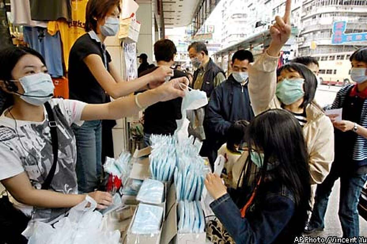 Vendors wearing surgical masks to try to protect themselves against severe acute respiratory syndrome, or SARS, sell masks in downtown Hong Kong Saturday, April 5, 2003. The deadly flu-like disease has killed 17 people and sickened nearly 700 in Hong Kong. (AP Photo / Vincent Yu)