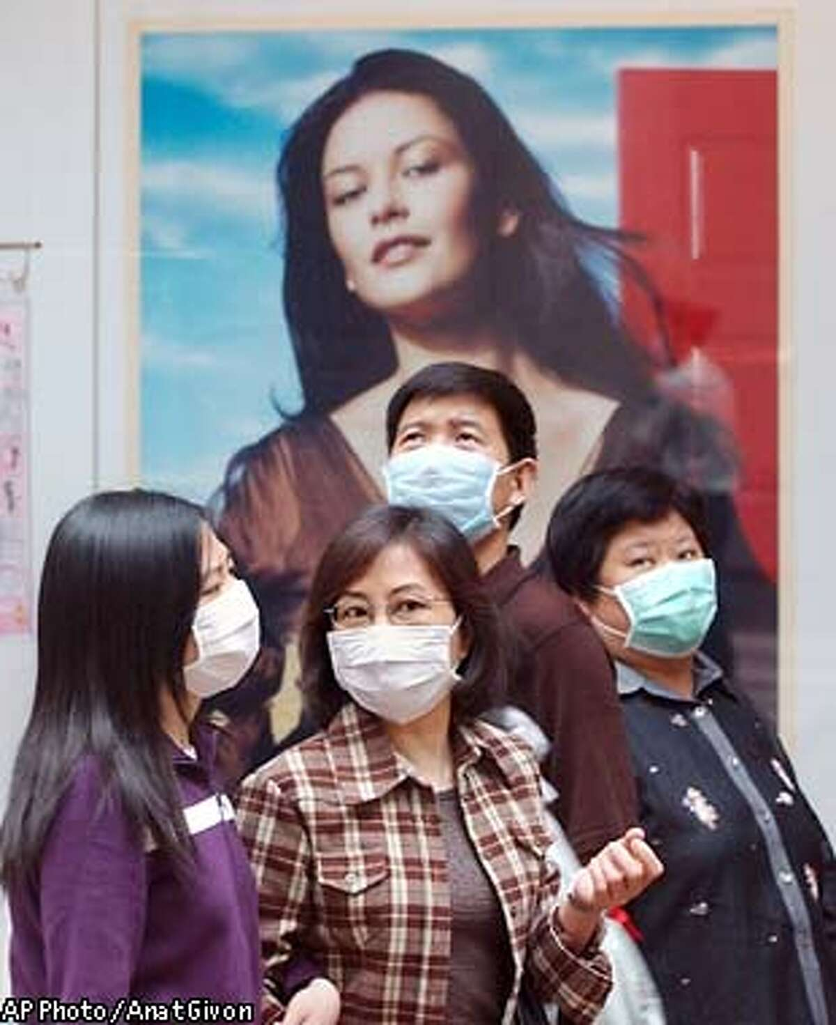 A group of people wearing surgical masks, to protect themselves from severe acute respiratoy syndrome, or SARS, stand in front of a cosmetics advertisment featuring oscar winning actress Catherine Zeta-Jones in a busy shopping district of Hong Kong, Saturday, April 5, 2003. Fears of the deadly flu-like disease are keeping many Hong Kong residents from travelling to China's neighboring Guangdong province, as tens of thousands do every year, for Ching Ming festival, a time when Chinese traditionally pay respect to the dead by cleaning their graves and burning incense. (AP Photo / Anat Givon)