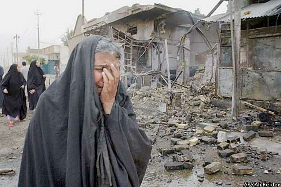 An Iraqi woman cries as she walks in front of a bakery that was destroyed in Baghdad Sunday, April 6, 2003. (AP Photo/Ali Heider) Photo: ALI HEIDER