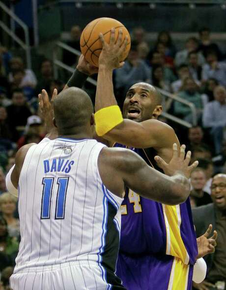 Lakers guard Kobe Bryant (right), who scored 30 points, takes a shot over Magic forward Glen Davis. Photo: AP