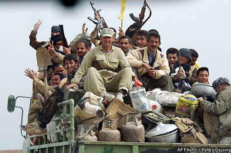 Kurdish fighters brandish their guns while riding atop a truck near the town of Kalak, in Kurdish-held northern Iraq, Saturday April 5, 2003. (AP Photo/Peter Dejong) Photo: PETER DEJONG