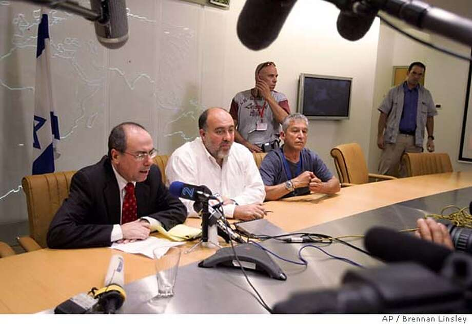 In front of members of the media, Israeli Foreign Minister Silvan Shalom speaks with the Israeli Ambassador in London about the earlier bomb attacks in London, inside the Israeli Foreign Ministry Emergency Situation Room, in Jerusalem, Thursday, July 7, 2005. Such discussions are common when there has been a significant terror attack abroad. Explosions rocked the London subway and one tore open a double-decker bus during the morning rush hour Thursday. (AP Photo/Brennan Linsley) Photo: BRENNAN LINSLEY