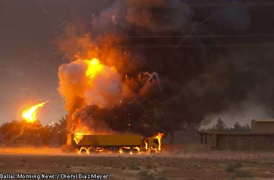 A semi-trailer truck full of ammunition is exploded by the Marines of the Second Tank Battalion during an advance on the outskirts of Baghdad on Friday, April 4, 2003. (AP Photo, Dallas Morning News/Cheryl Diaz Meyer) Photo: CHERYL DIAZ MEYER