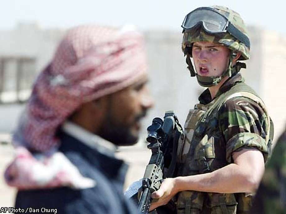 A British soldier watches an Iraqi civilian whilst accompanying Captain Ken Jolley, unseen, on a Hearts and Minds mission in southern Iraq, Friday, April 4, 2003. (AP Photo/ Dan Chung/Pool) Photo: DAN CHUNG