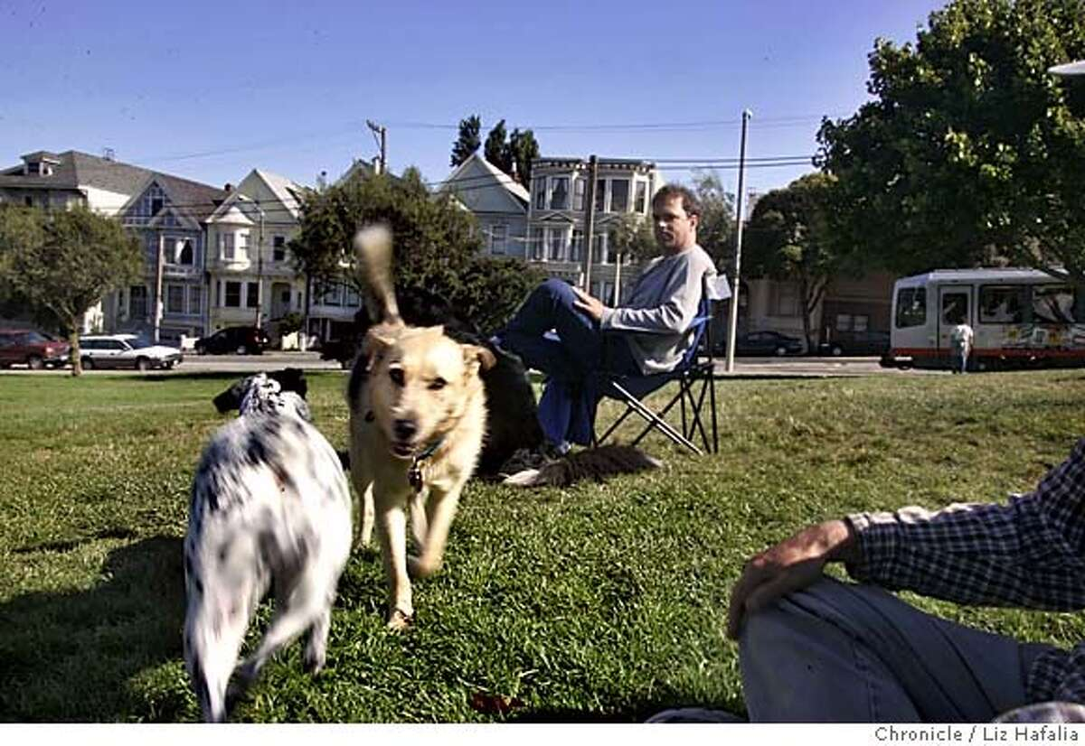 DOGPARK_029_LH.JPG Lily (left) an Australian cattle dog playing with Joesy (middle, cq) a shepherd mix, at Duboce Park. Lily's owner, John Lyman --(415)218-9379--sitting in chair. The Recreation and Parks Department shop around a habitat preservation plan proposing to shrink some off-leash parks. Mediation in the decade-long debate over a fenced dog run in the toddler-popular Duboce Park in the Castro is being discussed. Photographed by Liz Hafalia on 6/30/05 in San Francisco, CA Creditted to the San Francisco Chronicle/Liz Hafalia