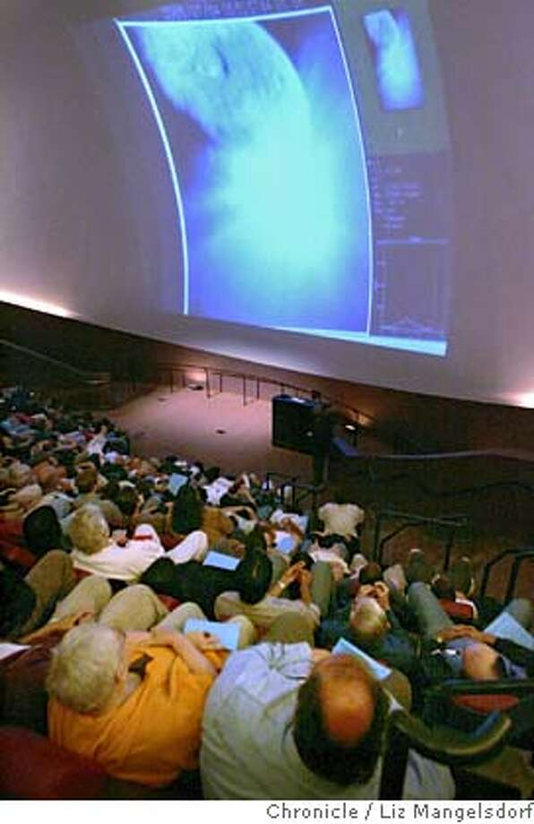 """Event on 7/3/05 in Oakland.  Visitors to Chabot Space and Science Center view pictures from the 820-pound """"impactor"""" Slamming into the comet Tempel 1. This is photo is taken in the Tien MegaDome Theater. Besides having live feeds from their own telescope, Chabot is having feeds from other NASA telescopes.  Liz Mangelsdorf / The Chronicle Photo: Liz Mangelsdorf"""