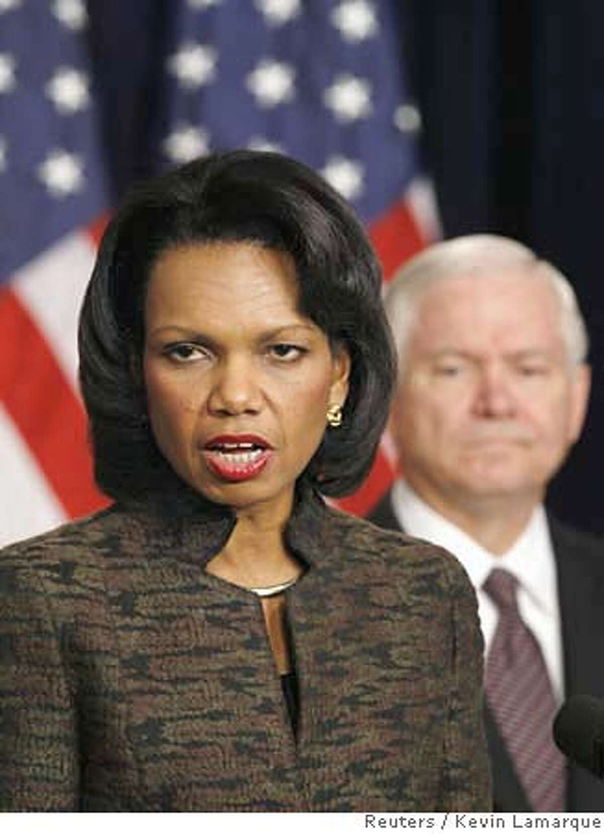 U.S. Secretary of State Condoleezza Rice (L) speaks to reporters about Iraq as Secretary of Defense Robert Gates watches at the Eisenhower Office Buildings in Washington January 11, 2007. REUTERS/Kevin Lamarque (UNITED STATES) 0