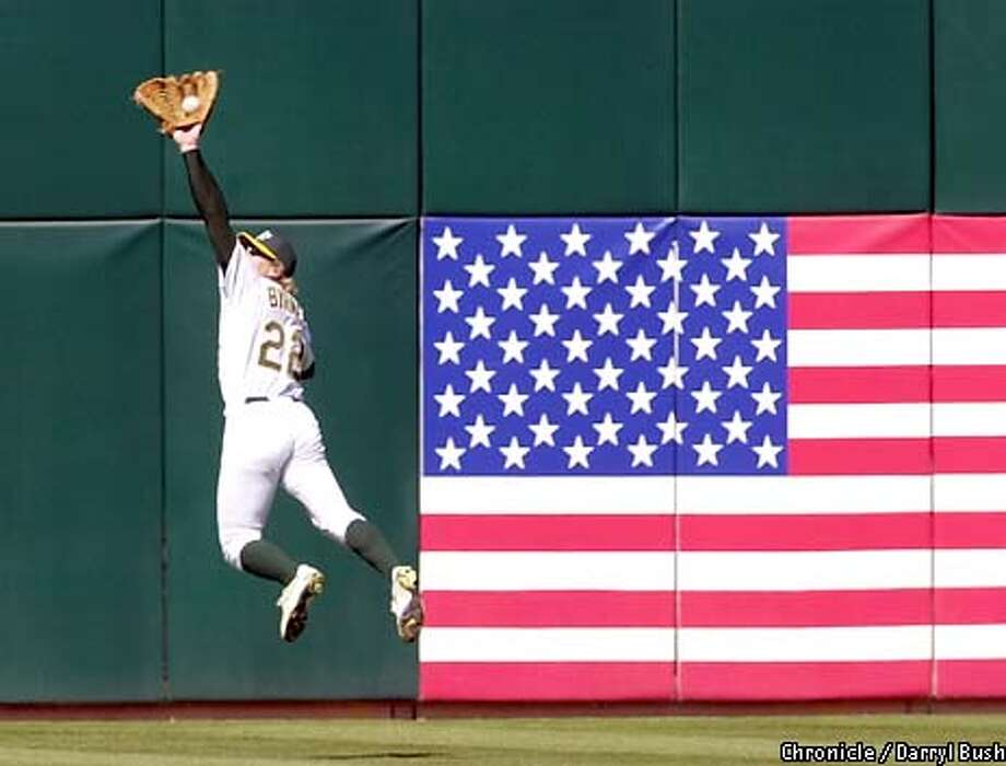 Athletics centerfielder Eric Byrnes dives high in the air to rob the Anaheim Angels ' Scott Spiezio of long hit to centerfield in the 4th inning at Oakland. Chronicle Photo by Darryl Bush Photo: Darryl Bush