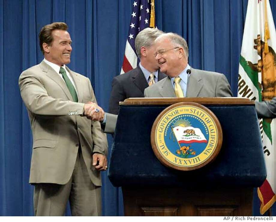 Gov. Arnold Schwarzenegger, left, shakes hands with state Senate Pro Tem Don Perata, D-Oakland, right, after Perata spoke to reporters about the budget compromise that had been reached, during a Capitol news conference in Sacramento, Calif., Tuesday, July 5, 2005. After meeting for more than 3 hours with legislative leaders, including Assembly Minority Leader Kevin McCarthy, R-Bakersfield, background, Schwarzengger announced that an agreement had been made on the roughly $116 billion 2005-06 spending plan, that still needs approval from both houses of the state Legislature. (AP Photo/Rich Pedroncelli) Ran on: 07-06-2005  Gov. Arnold Schwarzenegger (left) shakes hands with Senate President Pro Tem Don Perata, D-Oakland, after the budget deal. Ran on: 07-06-2005  Gov. Arnold Schwarzenegger (left) shakes hands with Senate President Pro Tem Don Perata, D-Oakland, after the budget deal. Ran on: 07-06-2005  Gov. Arnold Schwarzenegger (left) shakes hands with Senate President Pro Tem Don Perata, D-Oakland, after the budget deal. Photo: RICH PEDRONCELLI