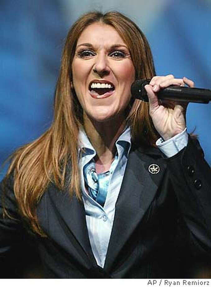 Celine Dion, wearing the new Air Canada flight attendant uniform, performs for employees at the airline's headquarters in Montreal on Tuesday, Oct. 19, 2004. The airline, which emerged from creditor protection last month, held the party for employees to show off its new uniforms and livery for its planes. (AP PHOTO/Ryan Remiorz, CP) Photo: RYAN REMIORZ