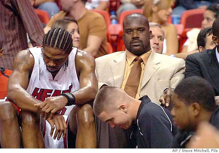 Miami Heat center Shaquille O'Neal (wearing tie) sits on the bench with teammate Miami Heat forward Udonis Haslem (40) in the fourth quarter after losing to the New York Knicks, 100-75, of an NBA basketball game Friday, Nov. 17, 2006, in Miami. The Heat announced Friday that O'Neal will undergo knee surgery,and will be out four to six weeks.(AP Photo/Steve Mitchell)  Ran on: 12-03-2006  Udonis Haslem and an injured Shaquille O'Neal haven't kept the NBA champion Heat from a terrible start.  Ran on: 12-03-2006  Udonis Haslem and an injured Shaquille O'Neal haven't kept the NBA champion Heat from a terrible start.  Ran on: 12-03-2006  Udonis Haslem and an injured Shaquille O'Neal haven't kept the NBA champion Heat from a terrible start.  Ran on: 12-03-2006 Photo: STEVE MITCHELL