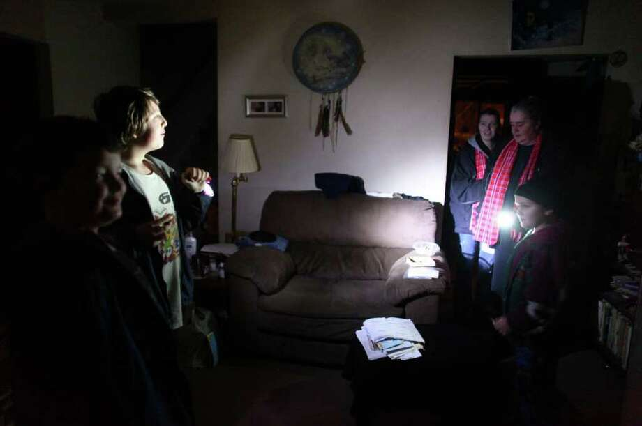 From left, Peyton Lucas, 6, Devon Lucas, 12, and Jonathan Lucas, 6, illuminate the interior of their home with flashlights on Friday, January 20, 2012 in Auburn. Power was out in the home. An ice storm wreaked havoc in the area, bringing down trees and power lines. Power was out in large parts of the area. Photo: JOSHUA TRUJILLO / SEATTLEPI.COM