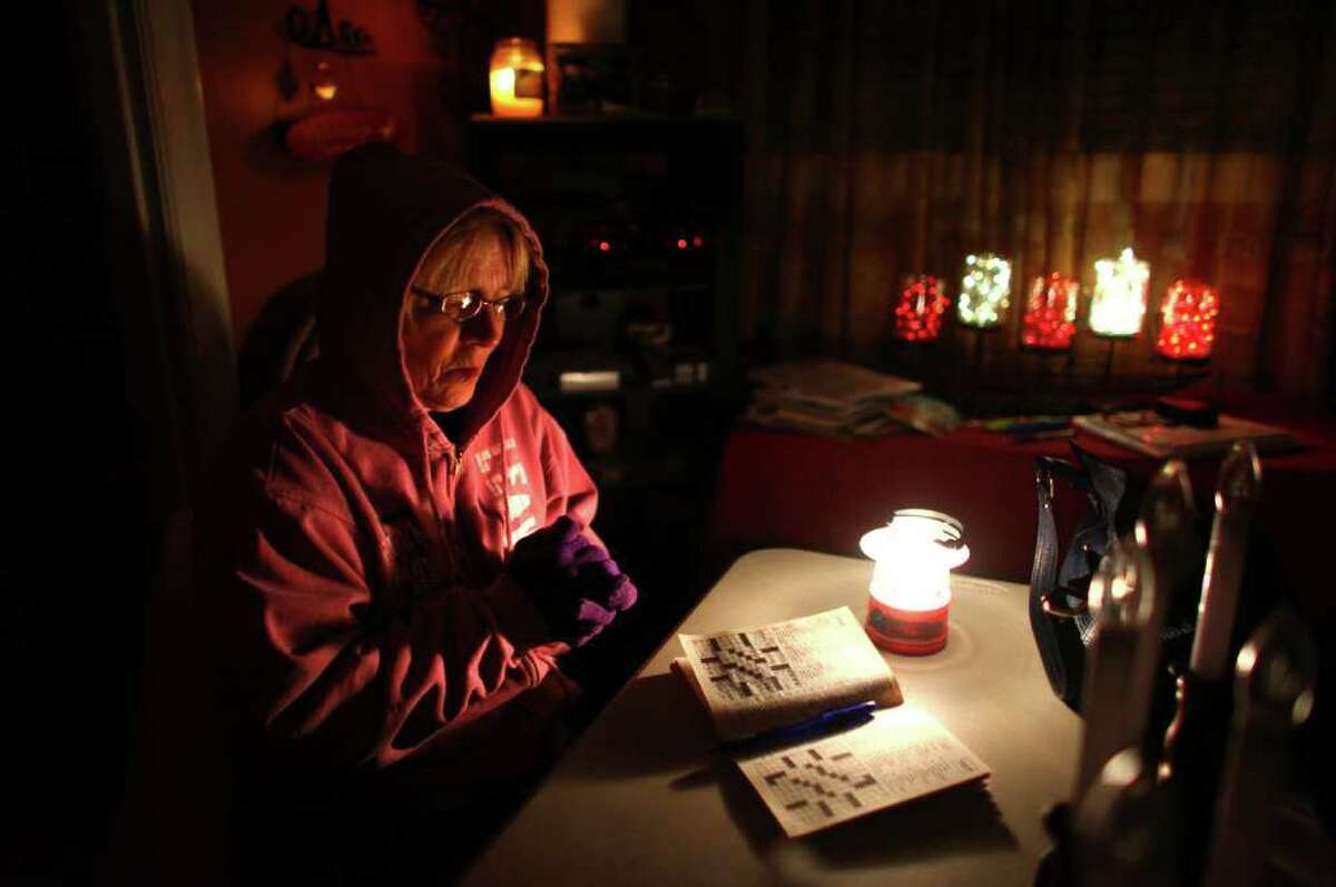 Doris Woodward warms her hands as she takes a break from a cross-word puzzle on Friday, January 20, 2012. Power was out in her home and she was without heat. An ice storm wreaked havoc in the area, bringing down trees and power lines. Power was out in large parts of the area.