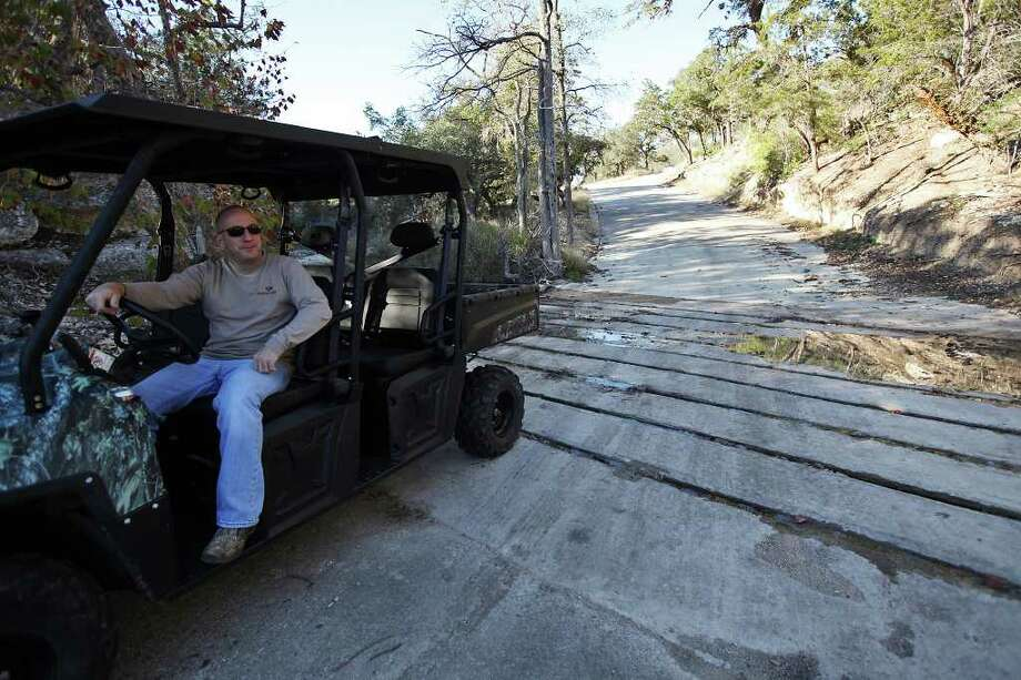 BIZ -- Lot owner Carl Dominguez sits by a low water crossing in the Clearwater Ranch subdivision in Northwest Bexar County, Wednesday, Nov. 30, 2011. Lots in the 11-acre plus range were sold by a developer that stopped work after selling many of the expensive home sites in the over 300-acres development. Now the owners of the lots are struggling to get CPS service and septic permits, and are dealing with a variety of bureaucratic issues such as golden checked warbler studies, an unauthorized low-water crossing, FEMA and U.S. Fish and Wildlife Although out in the county, the property lies within the city's ETJ zone and they won't let the owner use the road unless a bridge is built over the crossing. JERRY LARA/glara@express-news.net Photo: JERRY LARA, San Antonio Express-News / SAN ANTONIO EXPRESS-NEWS