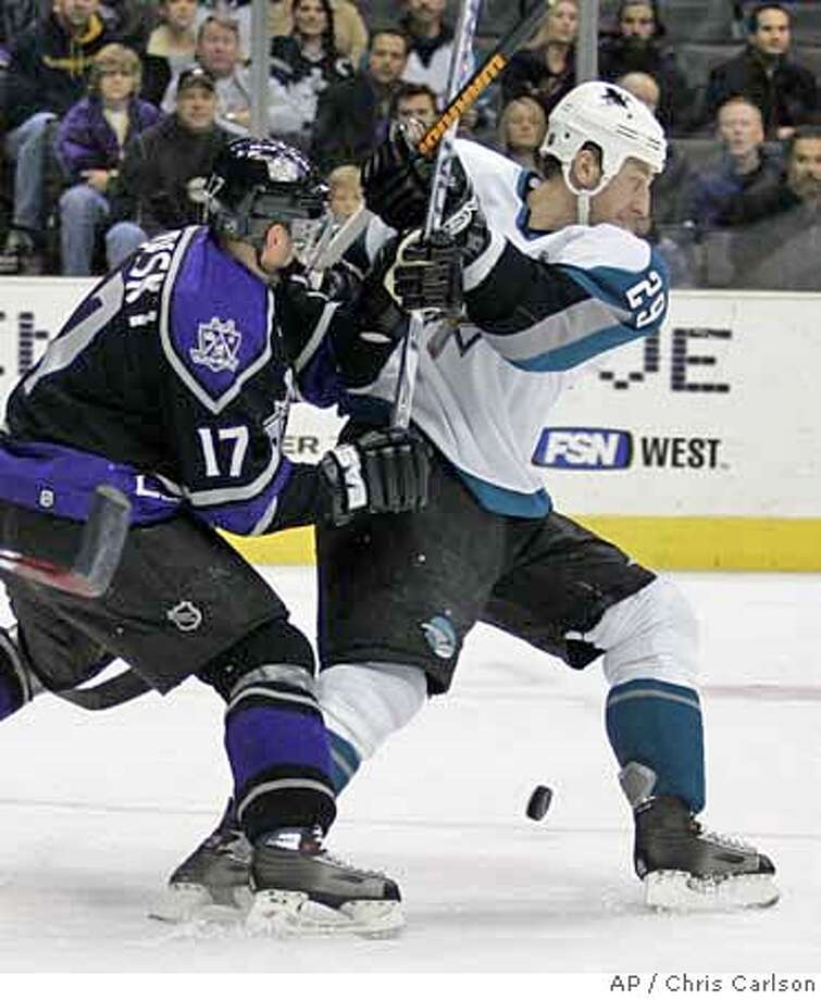 Los Angeles Kings defenseman Lubomir Visnovsky, left, battles San Jose Sharks right wing Ryane Clowe for th the pick during the first period of their NHL hockey game in Los Angeles, Thursday, Jan. 11, 2007. (AP Photo/Chris Carlson) Photo: Chris Carlson