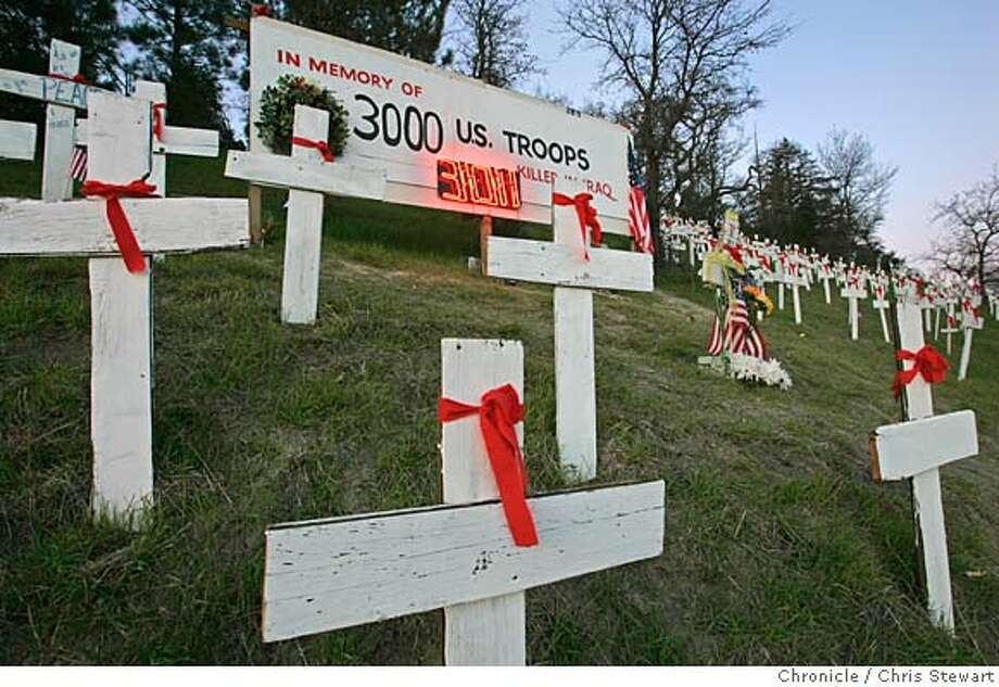 "A newly installed neon sign reads a current toll of 3011 U.S. troops killed in Iraq at a hillside memorial above the Lafayette BART station on Highway 24. The controversial memorial also features wooden crosses, Stars of David and Muslim crescent moons � representing the faiths of the war dead. ""Let's hope they don't have to add another digit"" said a passerby walking his dog near the hill.  Chris Stewart / The Chronicle Photo: Chris Stewart"