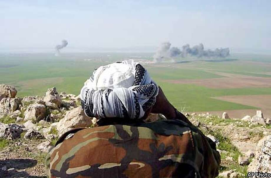 A peshmerga, a traditional Iraqi Kurdish fighter, watches an area after the bombardements of U.S warplanes in Domis between Dohuk and Mosul in northern Iraq on Wednesday, April 2, 2003. (AP Photo)