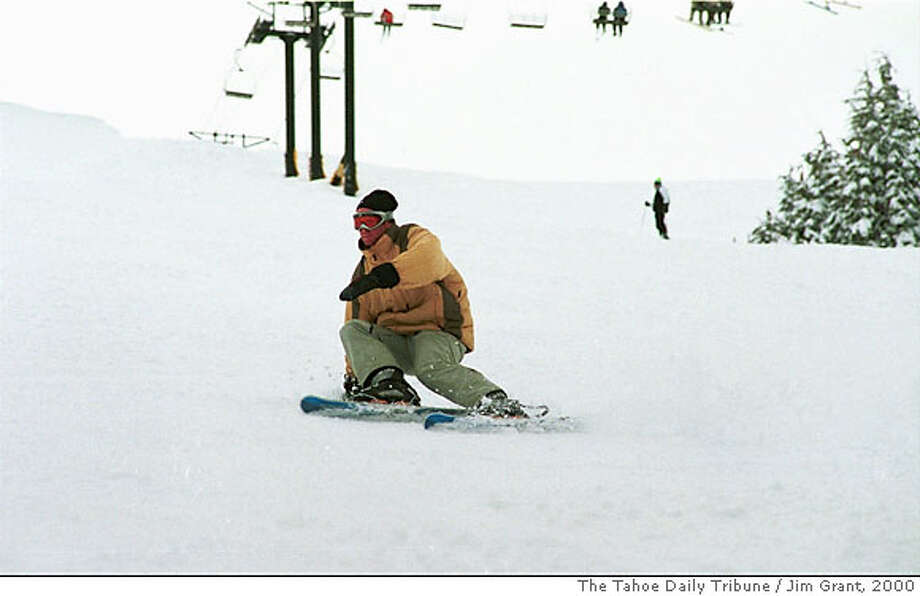 ADVANCE FOR WEEKEND OF NOV 25-26--FILE--A skier heads down a slope at Kirkwood ski resort near South Lake Tahoe, Calif., in this March, 2000 file photo. The ski lift behind the skier was recently replaced with a high-speed lift with gondolas that hold four persons each. Ski areas nestled around the Lake Tahoe Basin are emerging from decades in the shadows of resorts in Utah and Colorado with a billion-dollar makeover centered on their namesake jewel. (AP Photo/The Tahoe Daily Tribune, Jim Grant, File) Photo: JIM GRANT