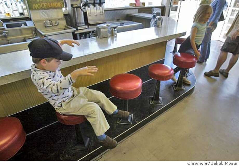 Will Haydel Strauch, 4, plays on a spinning chair at the closed Ozzie�s Soda Fountain counter. Believed to be the last drugstore lunch counter in the Bay Area, the 84-year-old institution in the Elmwood Health & Mercantile closed last week, having lost its soda jerk.  Event on 7/2/05 in Berkeley. JAKUB MOSUR / The Chronicle Photo: JAKUB MOSUR