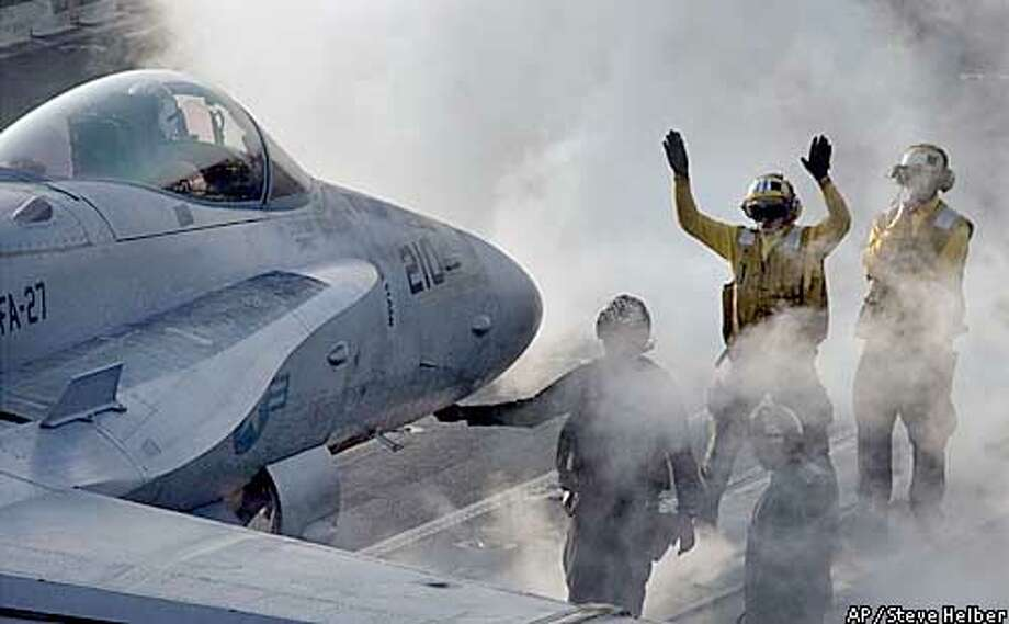 A flight deck crewmember signals an F/A-18C Hornet as it is prepared for launch off the flight deck of the aircraft carrier USS Kitty Hawk in the Gulf, Tuesday April 1, 2003. Planes from the ship continue to fly missions over Iraq in support of Operation Iraqi Freedom. (AP Photo/Steve Helber) Photo: STEVE HELBER