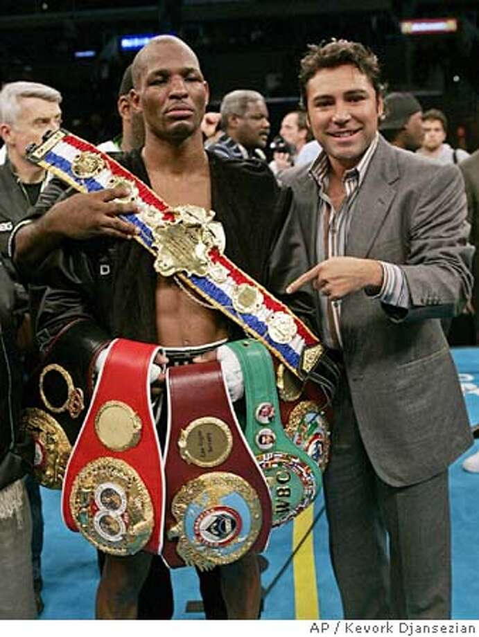 Boxer and fight promoter Oscar De La Hoya, right, points to the championship belts of Bernard Hopkins after Hopkins defeated Britain's Howard Eastman to retain the undisputed middleweight title in Los Angeles, Saturday, Feb. 19, 2005. (AP Photo/Kevork Djansezian) Ran on: 02-20-2005  Bernard Hopkins displays the championship hardware he defended for the 20th time. Photo: KEVORK DJANSEZIAN