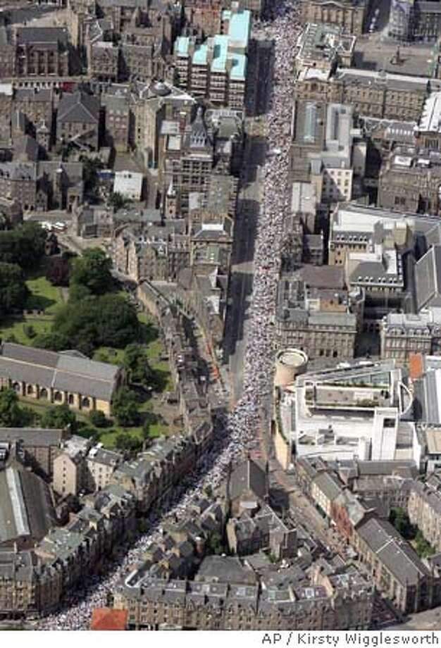 """Some of the 200,000 campaigners who formed a human chain around Scotland's medieval capital Edinburgh, on Saturday, July 2, 2005, demanding that the world's most powerful nations lift Africa out of poverty. Launching a week of demonstrations ahead of the G-8 summit, the """"Make Poverty History"""" march piles pressure on U.S. President George W. Bush and other leaders to end the misery of millions in the developing world. A river of protesters clad in white streamed through the cobbled streets of the Old Town, over the Royal Mile and through the commercial district, encircling Edinburgh Castle with a giant human bracelet in white, the symbol of the anti-poverty campaign. (AP Photo/Kirsty Wigglesworth/PA) ** UNITED KINGDOM OUT ** Photo: KIRSTY WIGGLESWORTH"""