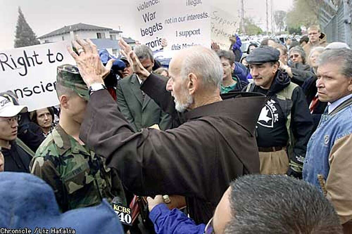 Stephen Funk, a volunteer reservist with the U.S. Marine Corps, gets blessed by father Lewis Vatale of St. Boniface/San Francisco before he enters the gates of 1st Beach Terminal Operations, 4th Landing Support Battalion in San Jose. He is publicly declaring his conscientious objector status. (PHOTOGRAPHED BY LIZ HAFALIA/THE SAN FRANCISCO CHRONICLE)