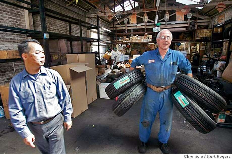 Tony Fung watches as John Rivelli takes some tire's as they are busy cleaning out their property.  Tony Fung owner of Autohouse and John Rivelli the owner of Rivelli Tire .Both businesses are being evicted using eminent domain to pave the way for a giant housing complex.  EVICT02_0119_kr.JPG 7/1/05 in Oakland,CA.  KURT ROGERS/THE CHRONICLE MANDATORY CREDIT FOR PHOTOG AND SF CHRONICLE/ -MAGS OUT Photo: KURT ROGERS