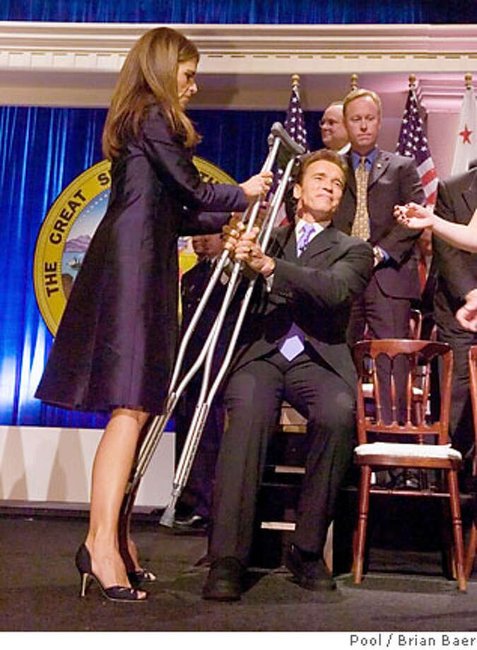 Maria Shriver takes the crutches away from husband California Governor Arnold Swarzenegger after he was sworn in for his second term at the Memorial Auditorium in Sacramento, California January 5, 2007. REUTERS/Brian Baer/Pool (UNITED STATES)  M & R CAPTION CONTEST Photo: POOL