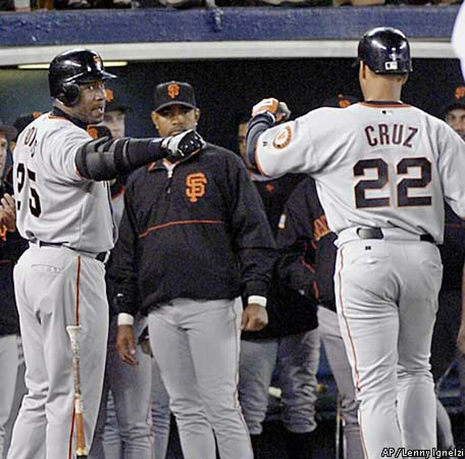 San Francisco Giants' Jose Cruz is met by teammate Barry Bonds, left, after blasting a solo home run in the fourth inning against the San Diego Padres Tuesday, April 1, 2003, in San Diego. (AP Photo/Lenny Ignelzi) Photo: LENNY IGNELZI