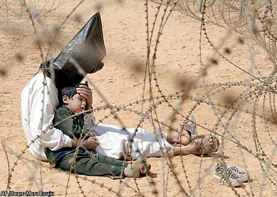 An Iraqi man comforts his 4-year-old son at a regroupment center for POWs of the 101st Airborne Division near An Najaf, Iraq Monday, March 31, 2003. The man was seized in An Najaf with his son and the U.S. military did not want to separate father and son. (AP Photo/Jean-Marc Bouju) Photo: JEAN-MARC BOUJU