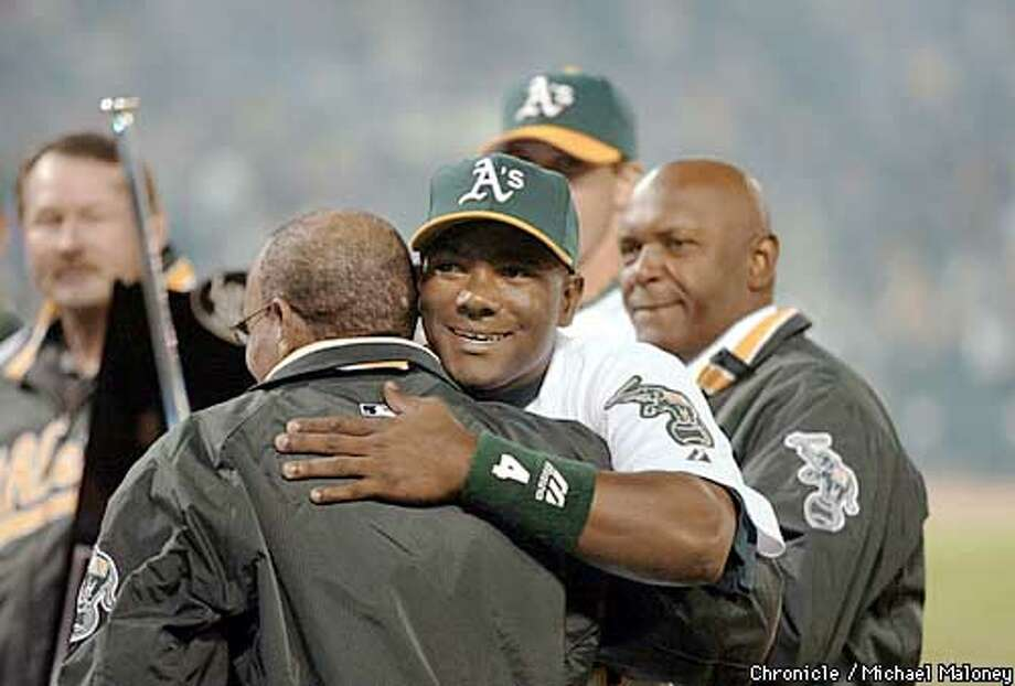 Miguel Tejada gets a hug from former A's star Bert Campanaris after recieving the AL MVP award from last season. In background from left is Carney Lansford, Barry Zito (partially hidden) and Vida Blue.  Oakalnd A's home opener against the Seattle Mariners at the Network Associates Coliseum.  CHRONICLE PHOTO BY MICHAEL MALONEY Photo: MICHAEL MALONEY
