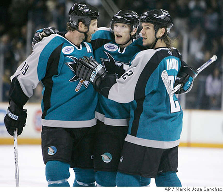San Jose Sharks defenseman Christian Ehrhoff, middle, of Germany, is hugged by teammates Joe Thornton, left, and Scott Hannan after Ehrhoff's goal in the second period of an NHL hockey game in San Jose, Calif., Saturday, Jan. 6, 2007. (AP Photo/Marcio Jose Sanchez) Photo: Marcio Jose Sanchez