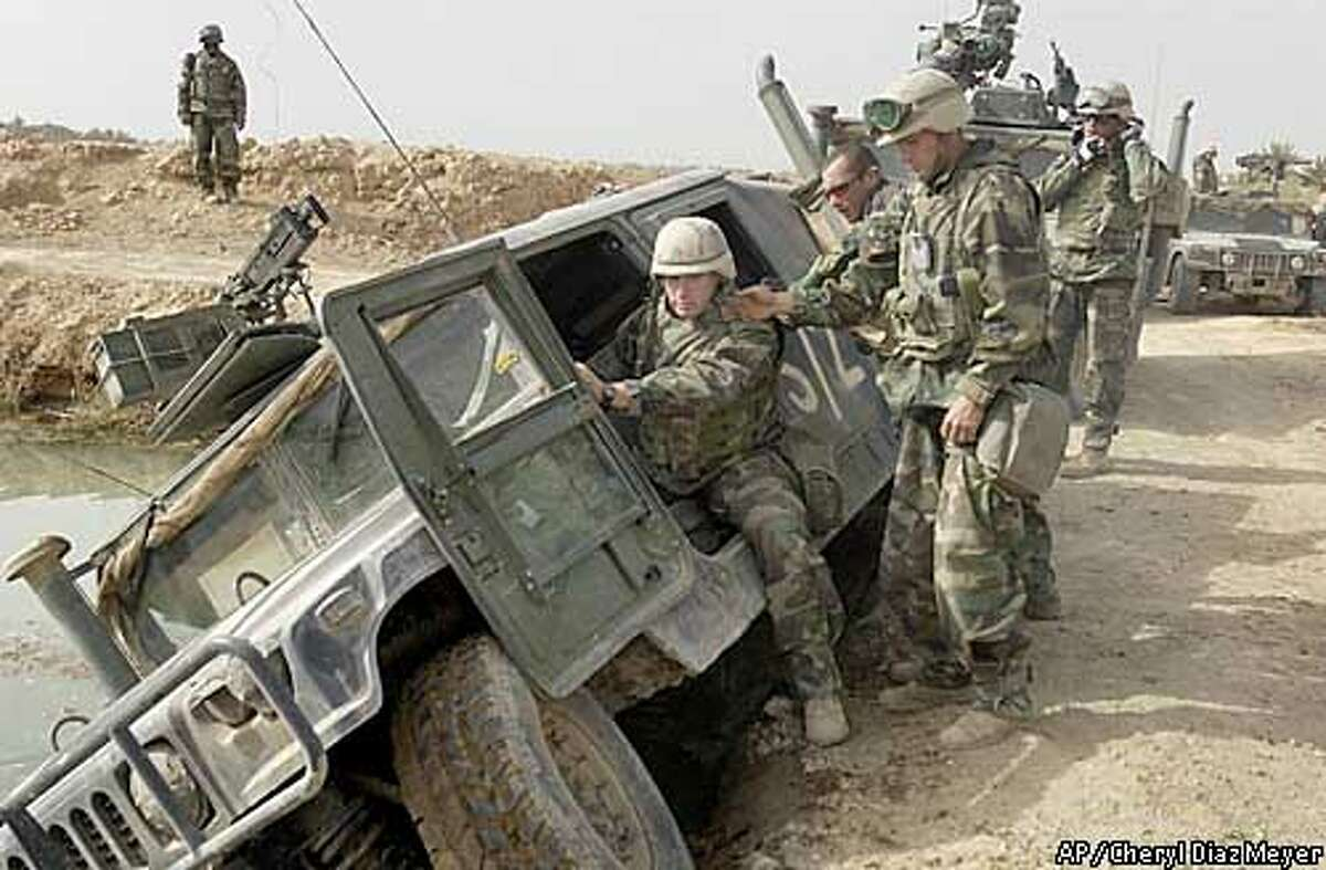 Marine scouts of the Second Tank Battalion pull a vehicle out of a ditch during a reconaissance mission some 75 miles south of Baghdad, on March 31, 2003. (AP Photo, Dallas Morning News/Cheryl Diaz Meyer)