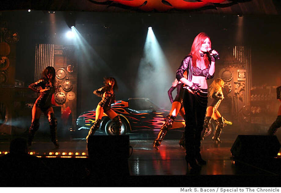 """Six Across - Some of the cast from Harrah's """"Rock My Ride"""" show join up on the set designed to look like an auto body shop. From left, they are Veronica Bisbee, Chelsea Thompson, Tim Tenhumberg, Chanel Keesling, Britney Irwin, and Sarah Roulias. Thompson and Tenhumberg are two of the show's singing stars. Photo: Mark S. Bacon/Special to The Chronicle  Ran on: 01-07-2007  &quo;Rock My Ride&quo; at Harrah's in Reno features classic cars and a cast of showgirls and singers. Photo: Mark S. Bacon/Special To The Chr"""