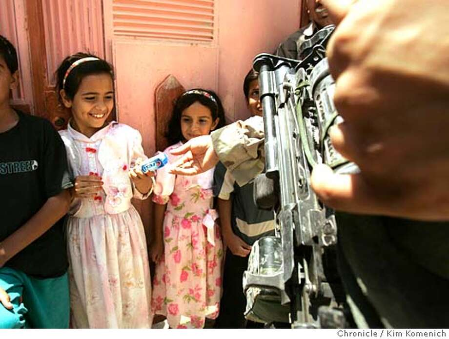 """Soldiers hand out toothpaste (and candy, go figure) to kids during a """"cordon and talk"""" mission.  Soldiers from Patrol Base Uvanni in Samarra, Iraq endure afternoon mortar attack as part of their day as they search suspected insurgents' homes, perform a """"cordon and talk"""" ( where they hand out candy and toothpaste to kids in a neighborhood they cordon off), and look for suspicious cars using tanks to halt traffic.  San Francisco Chronicle photo by Kim Komenich Photo: Kim Komenich"""