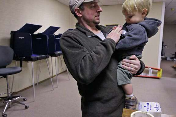 Ted Grimes, left, of Anderson, S.C., places an I Voted sticker on the coat of his son Sawyer Grimes, 1, Friday, Jan. 20, 2012, in the Anderson County Voter Registration office, after voting absentee in the Republican presidential primary, in Anderson, S.C.  (AP Photo/Anderson Independent-Mail, Ken Ruinard) GREENVILLE OUT SENECA OUT